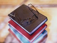 High angle view of stack of books with eyeglasses resting on top